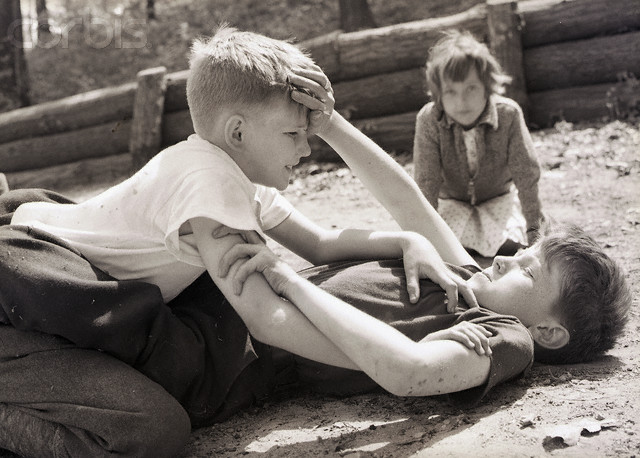ca. 1940s --- Original caption: Two boys lie on the ground fighting, as a girl watches eagerly in the background.  Photograph circa 1940s. --- Image by © Bettmann/CORBIS